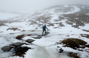 Ian Homer Photography. Ben Lomond climb: crossing the frozen burn (stream) on stepping stones between the Ptarmigan Ridge and the summit bloc.