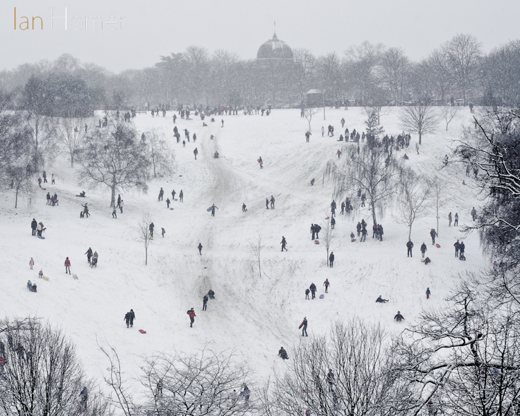 Slopes covered in people enjoying the weekend snow at Greenwich Park, London, in the shadow of the Royal Observatory.