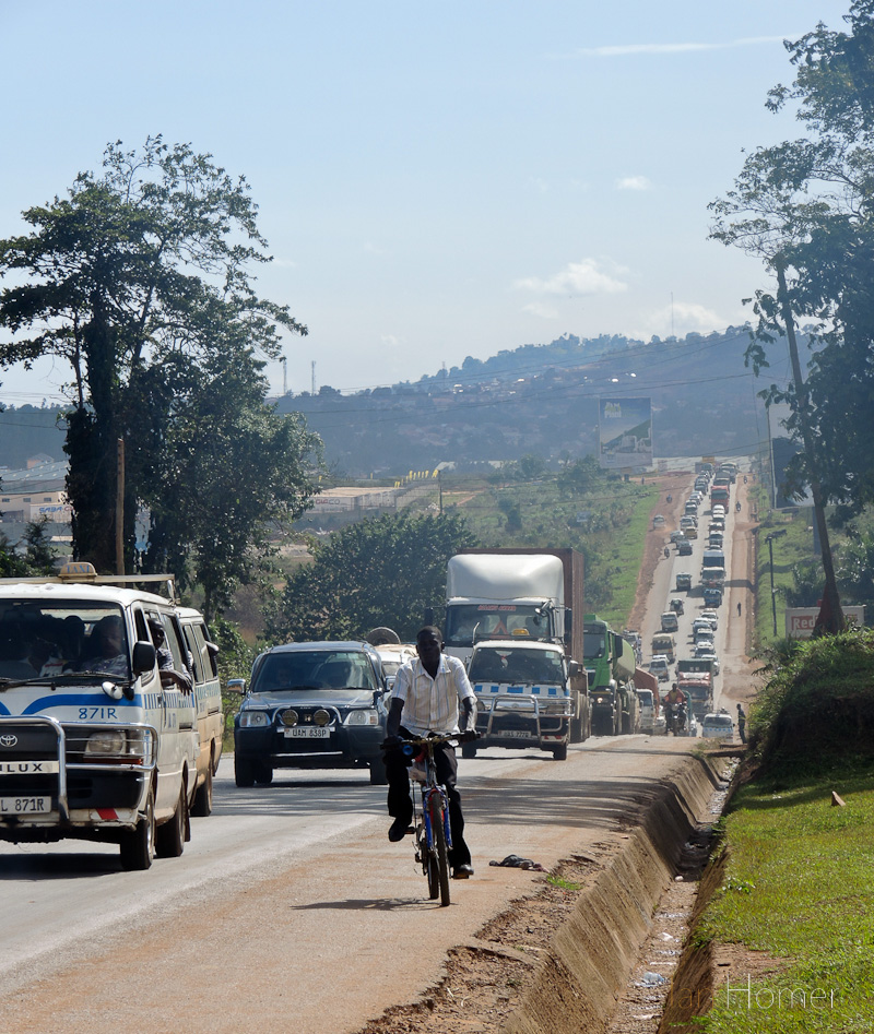 A cyclist makes his way up the shoulder of the shoulder of the congested Kampala - Jinja Highway near Namanve
